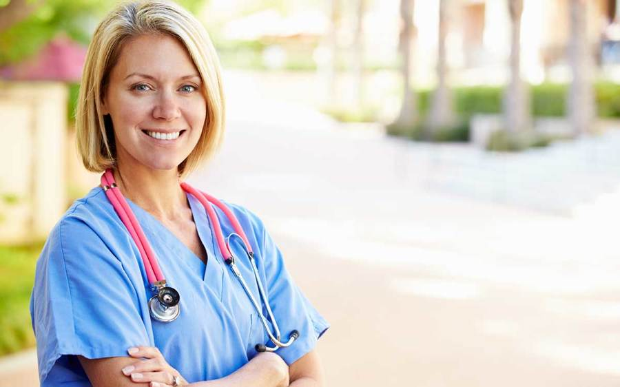 A nurse in blue scrubs stands outside, representing the best health care workplaces in the US.