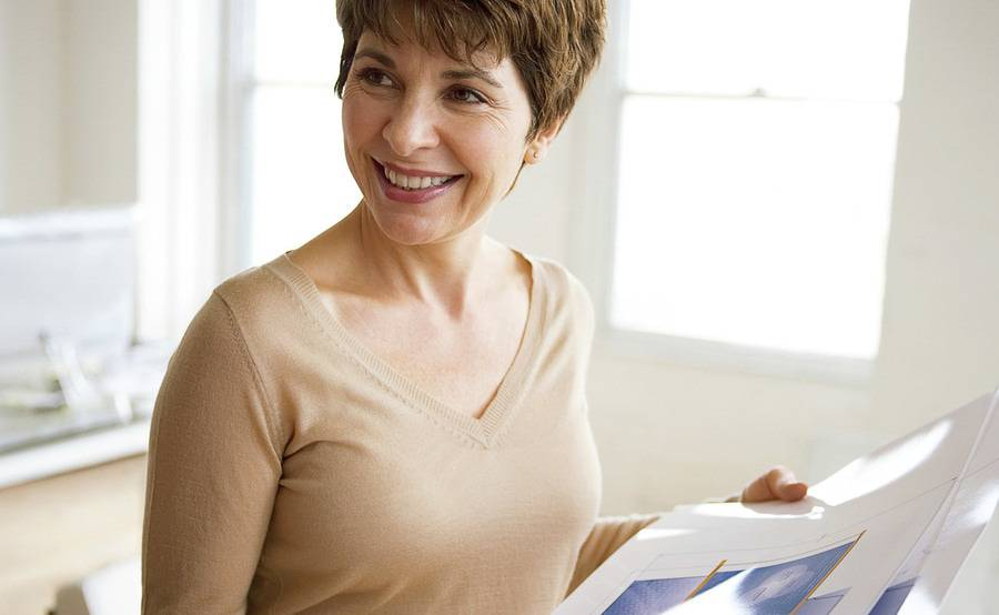 A smiling mature woman represents a healthier life with treatment for bladder incontinence treatment.