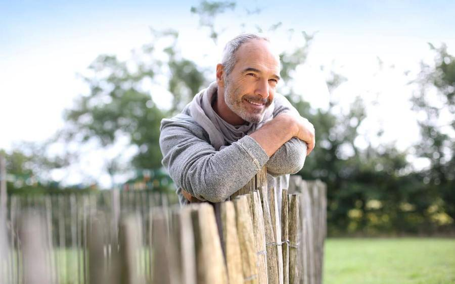 Older man leans against a wooden fence and smiles to signify he's happy   with his prostate cancer treatment.