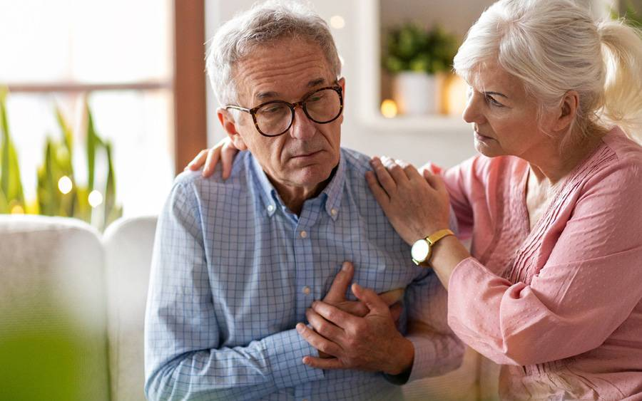 Older man grabbing his chest in pain with his wife coming to his aid.