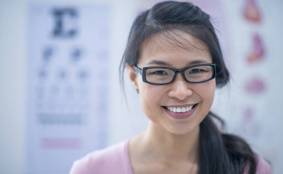A young woman with glasses smiles in front of an eye chart, representing how you can see your best with ophthalmology and optometry care from Scripps in San Diego.
