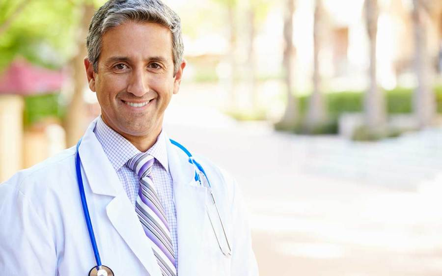 A physician stands in an outdoor setting with a white lab coat and blue stethoscope.