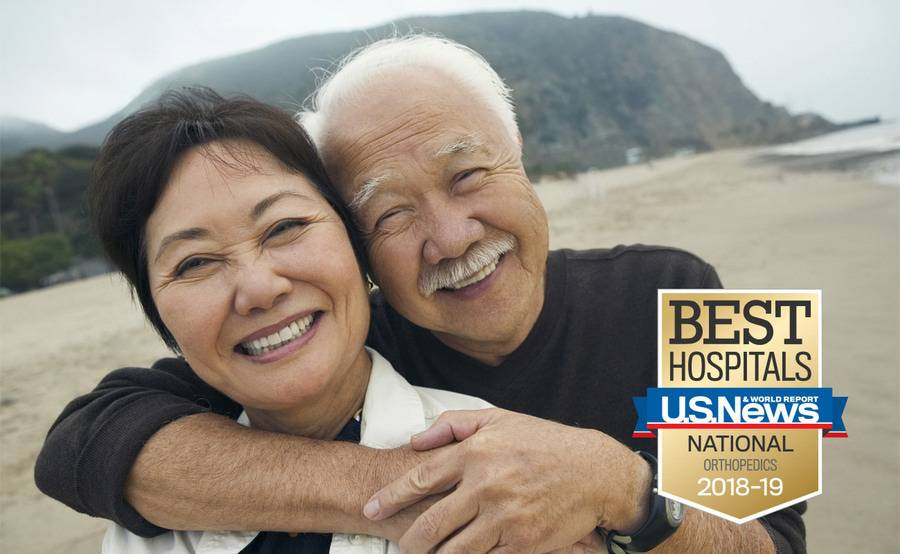 A smiling mature Asian couple on the beach represents the active life that can be led after surgery for elbow, wrist or hand injuries.