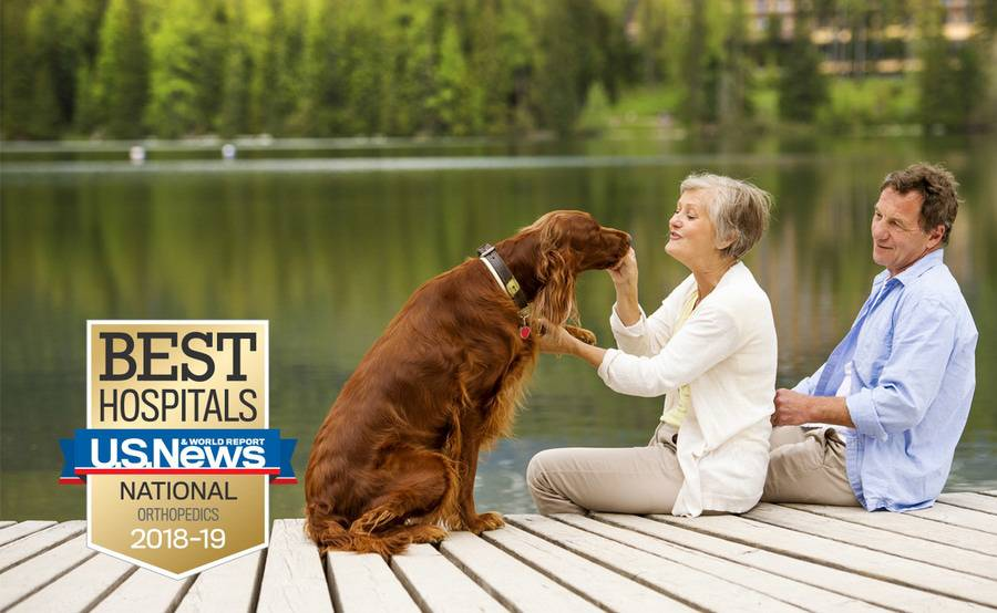 A mature couple sits on a dock and plays with their dog, representing the full life that can be led after joint reconstruction or joint replacement.