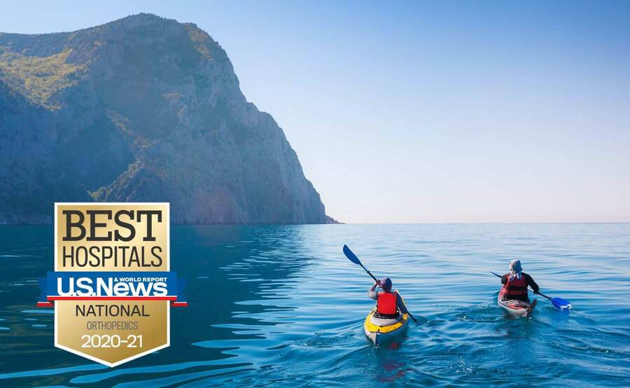Two people paddle their kayaks around a mountain, representing an actively lifestyle after shoulder surgery.