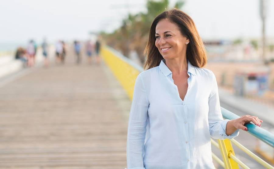 A smiling middle-aged woman stands down a boardwalk, representing a healthier life with treatment for PAD.