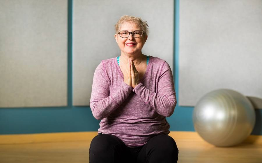 Scripps Health patient Pamela Underwood kneels on yoga mat with her hands pressed against her heart and a balance ball visible in the background in a fitness studio environment