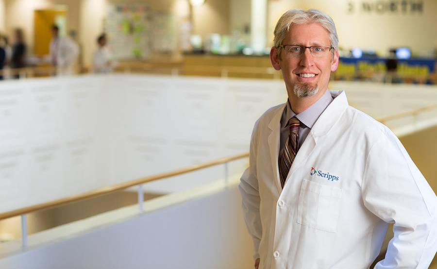 Jonathan Fisher, MD, stands in a bright, modern atrium, representing advanced pancreas transplant care at Scripps.