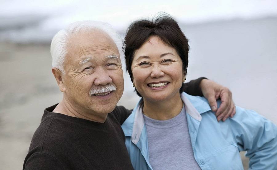 A smiling mature Asian couple represents the full life that can be led after pancreatic neuroendocrine tumor treatment.