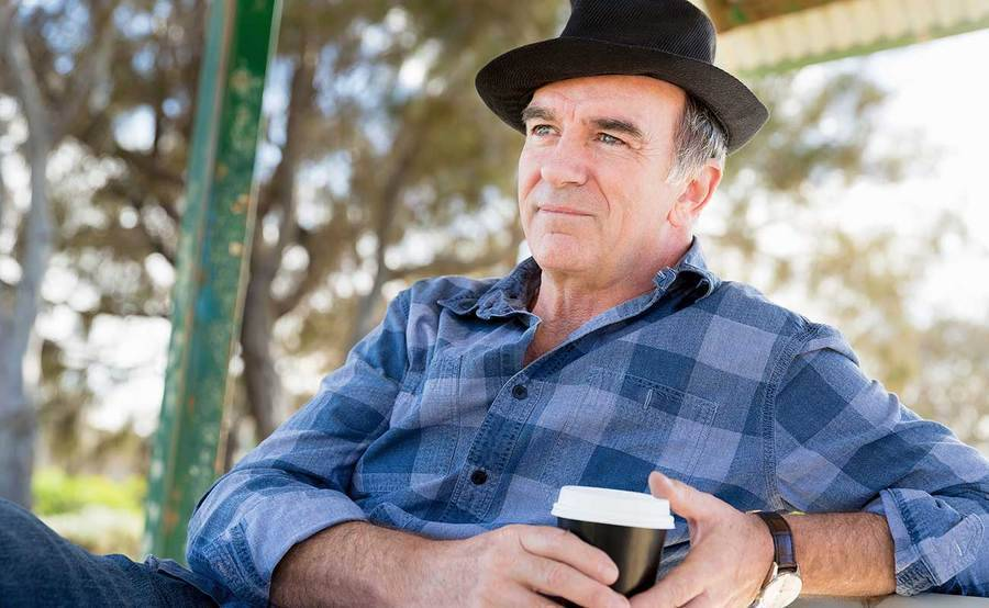 A smiling middle-aged man drinking coffee in a park represents the full life that can be led after parathyroid cancer treatment.
