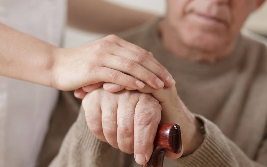 Caregiver holds hand of elderly man with Parkinson's disease.