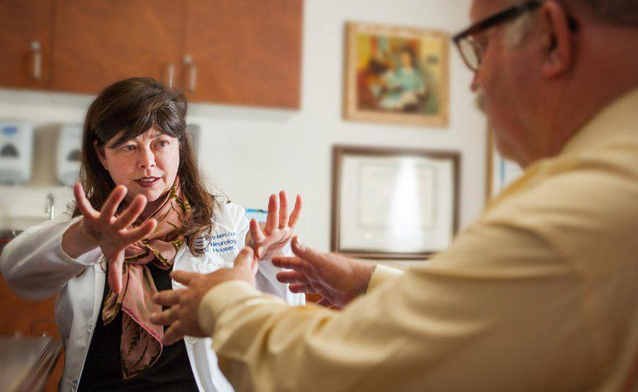 Scripps neurologist Dr. Melissa Houser assesses a man for hand tremors related to Parkinson's disease, representing the expert, compassionate care received at Scripps.