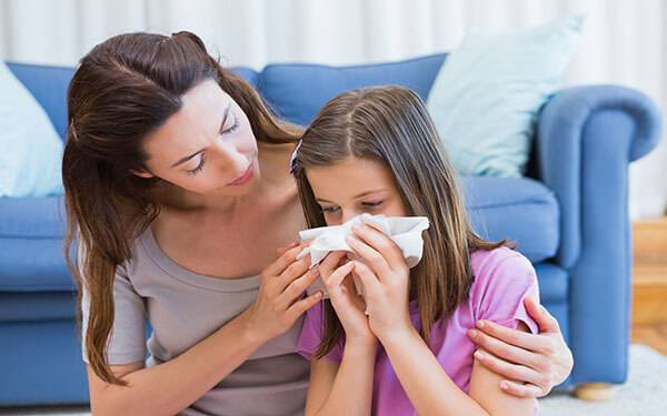 Mother holding Daughter with allergies indoors