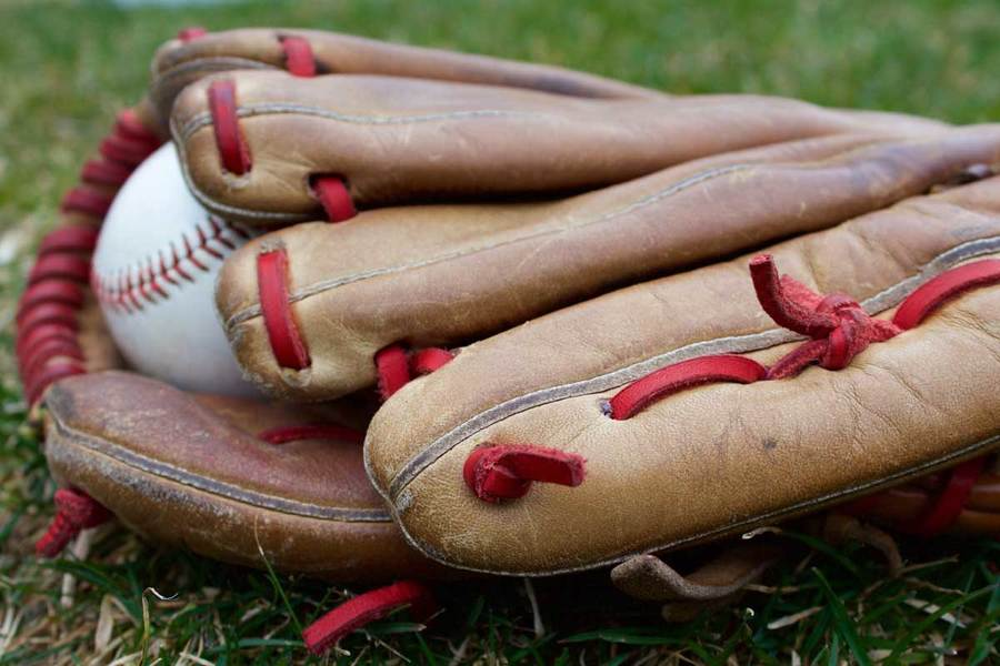 Baseball glove and baseball lying on the grass; baseball is among the sports for which athletes might jeopardize their health by taking performance enhancing supplements.