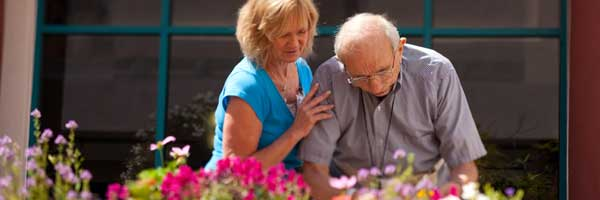 An elderly male patient receives assistance cutting flowers from a professional rehabilitation therapist.