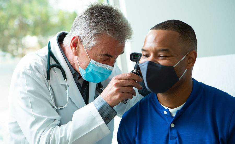 Physician performing an ear examination, with a face mask, on a patient also wearing a mask.