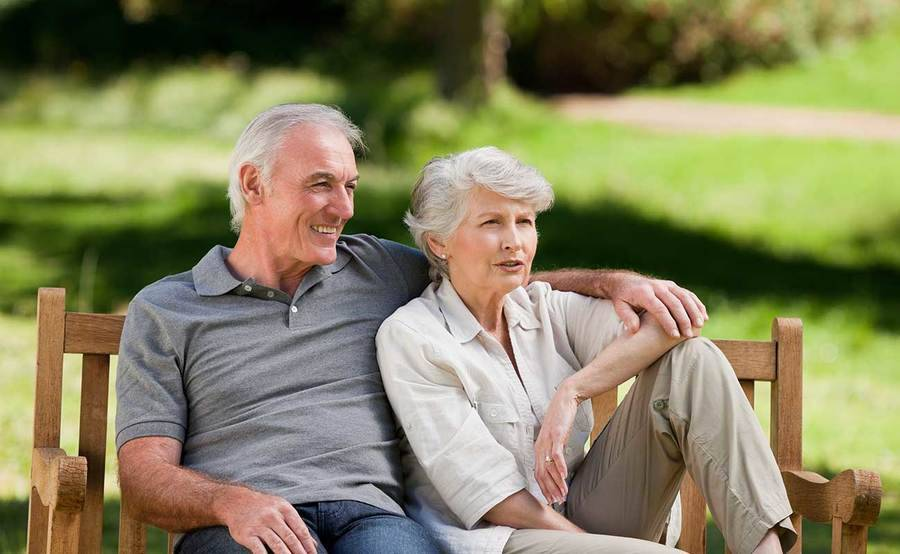 A mature couple on a park bench represent the full life that can be led after pituitary cancer treatment.