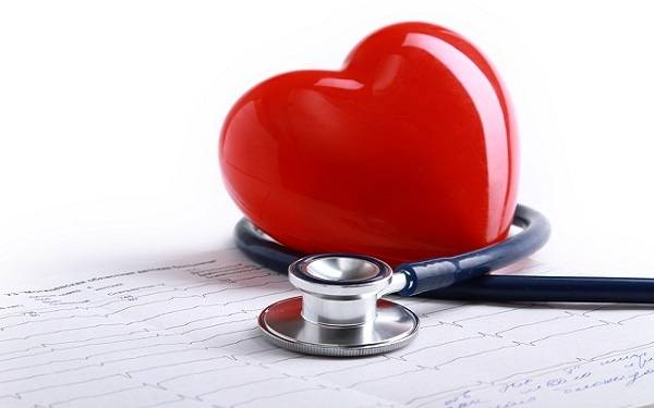 A stethoscope and red heart lie on top of an EKG strip, representing the importance of heart screenings for women.