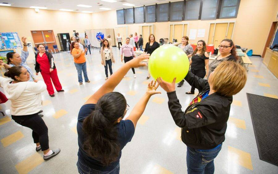 Members of the Scripps Prediabetes Program stand together in a large circle and enjoy a fun ball exercise.