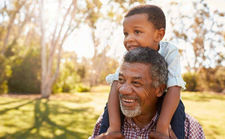 A mature African-American man with grandson represents the power and value of knowing prostate cancer symptoms.