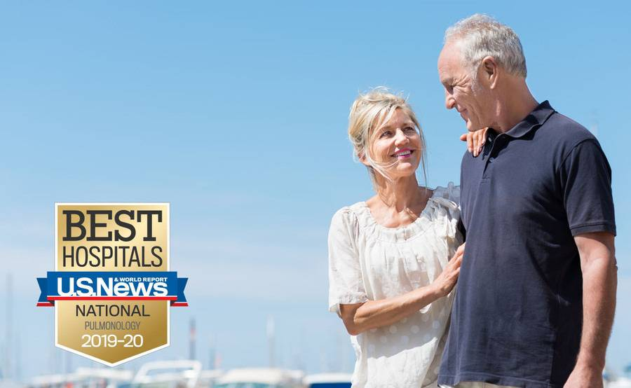 A mature couple walks along a marina, representing the healthy results of managing your respiratory disorder.