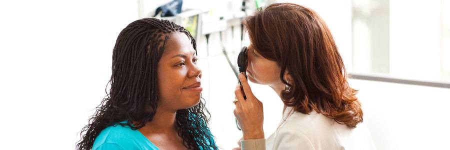 A middle-aged woman gets her eyes checked by a Scripps doctor, who is providing high-quality care.