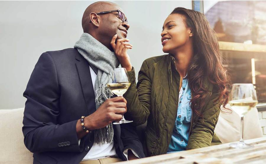 A man enjoys a glass of heart-friendly white wine with his partner in an outdoor coastal setting.