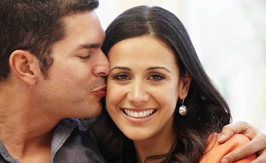 A middle-aged man kisses a smiling woman's cheek, representing the full life that can be led after reconstructive surgery.