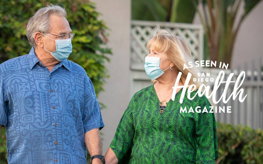 Cherie and Larry Eyer hold hands as they walk in front of their home while being monitored by Scripps during their COVID recovery.