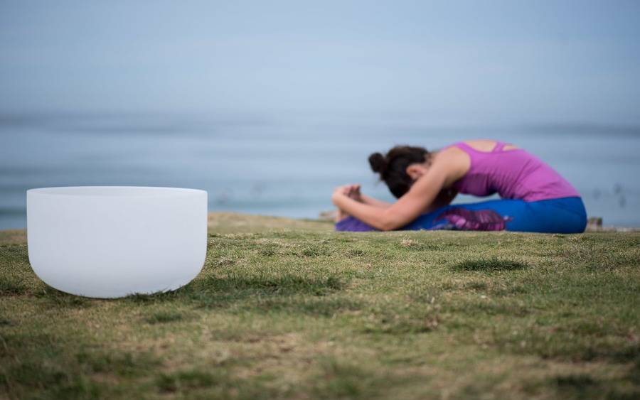 A woman practices a seated yoga pose in the background next to a singing bowl, representing the healing atmosphere of restorative yoga.
