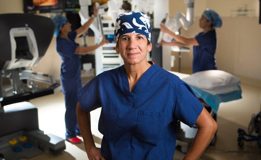 Dr. Carol Salem stands in a Scripps operating room while a team uses a robotic surgical system.
