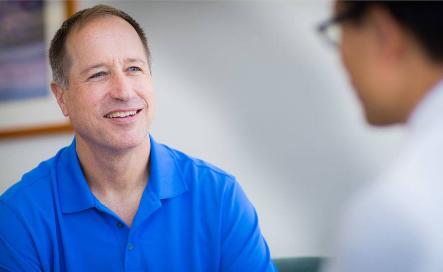 A smiling middle-aged man talks with his surgeon, representing advanced robotic prostate surgery at Scripps.