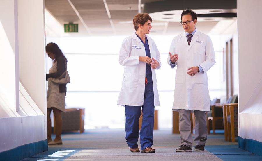 Two doctors talk while walking in a sunny corridor, representing collaborative robotic urologic surgery at Scripps.