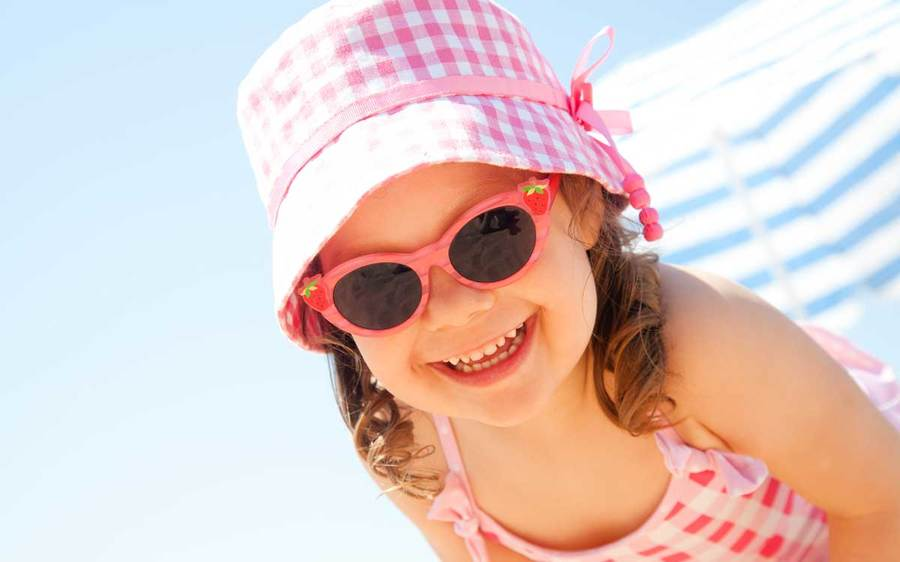 A young girl wearing sunglasses and a sun hat enjoys a day at the beach in San Diego.