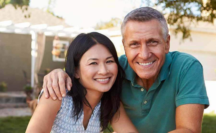 A smiling middle-aged Caucasian man and Asian woman represent the full life that can be led after treatment for sarcoma or bone cancer.
