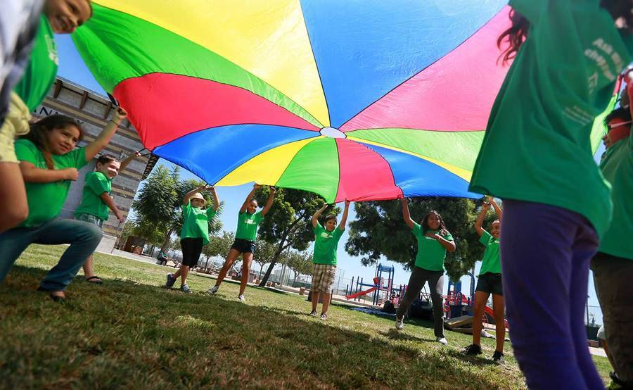Children play with a large, colorful parachute in a park, representing the impact of our community health programs.