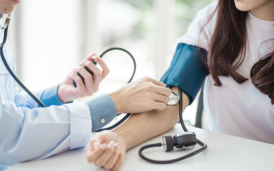 A doctor checks a woman's blood pressure as it relates to a Scripps MD who addresses key issues about women's heart health.