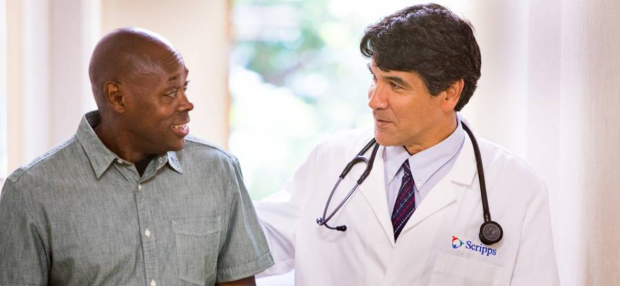 Dr. Gerard Lumkong talks with a man in a bright, sunny hallway, representing the expert, collaborative primary care at Scripps Coastal Medical Center.