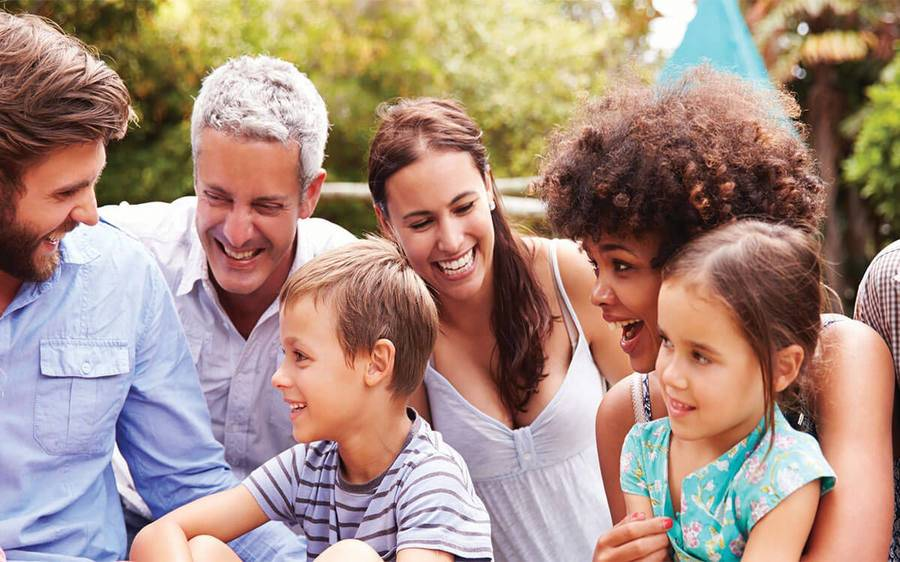 group of diverse adults and kids laughing outdoors