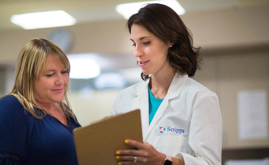 A nurse practitioner with a clipboard talks with a female patient at a Scripps walk-in clinic that offers care for minor illnesses and injuries.