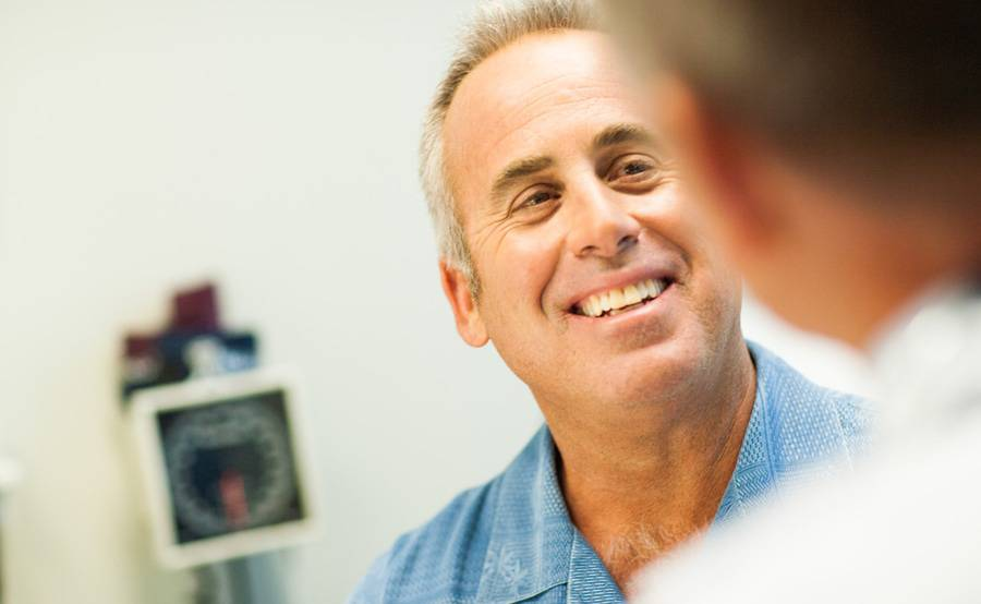 A middle-aged man meets with a nurse practitioner at a Scripps walk-in clinic, which offers care for minor illnesses and injuries.