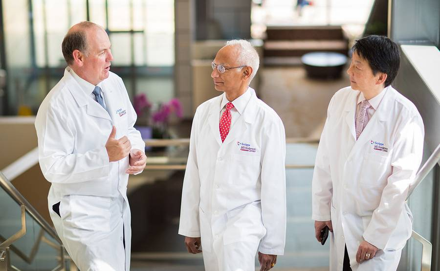 A group of radiation oncologists in discussion represents the team of cancer experts who will care for you at Scripps MD Anderson.