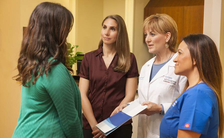 A team of oncology nurses hands an informational packet to a patient, representing the guidance and support you receive at Scripps MD Anderson Cancer Center.