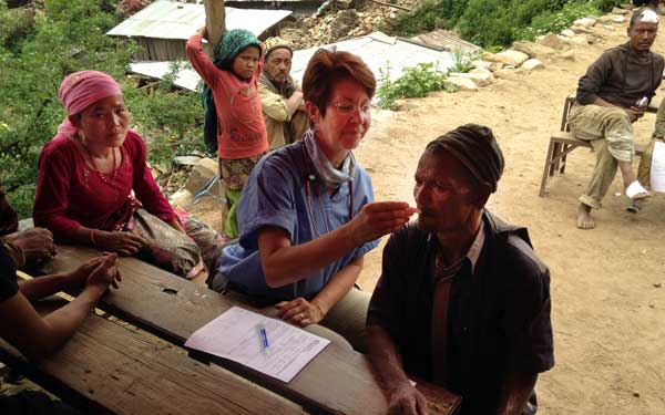 Scripps Health Medical Response Team member Debra McQuillen examines patients at a temporary medical clinic set up in a remote Nepal village damaged by the recent earthquakes. (Photo credit: Scripps Health) View high-resolution image