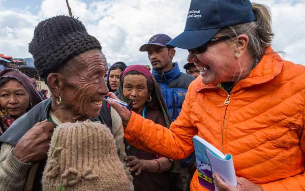 Scripps Health Medical Response Team member Jan Zachry, RN, greets a man after arriving by helicopter in a remote mountainous village damaged by the recent earthquakes in Nepal. (Photo credit: International Medical Corps). View high-resolution image
