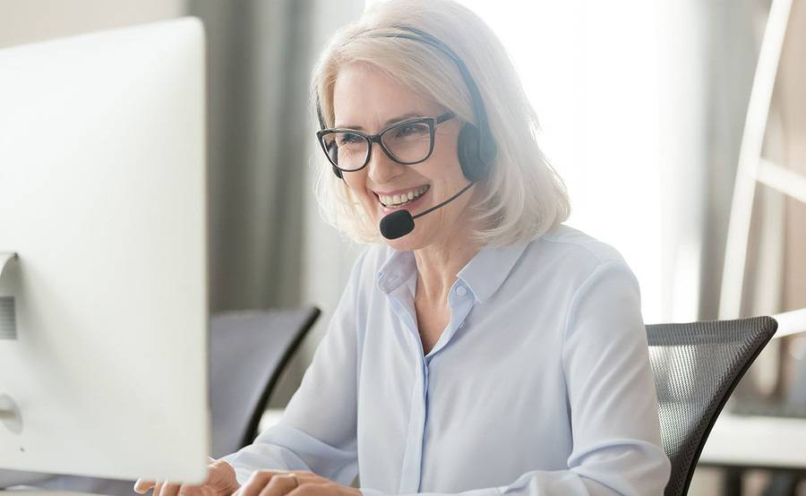 A mature woman working as a patient transfer support specialist discusses a case through her headset while typing notes.