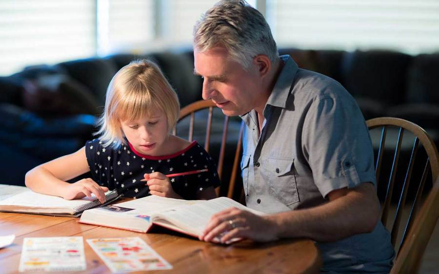 A father helps his daughter with her homework.