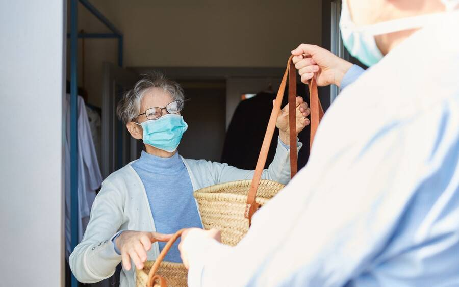 A caregiver wearing mask gives senior also wearing a mask a basket of food during coronavirus pandemic.