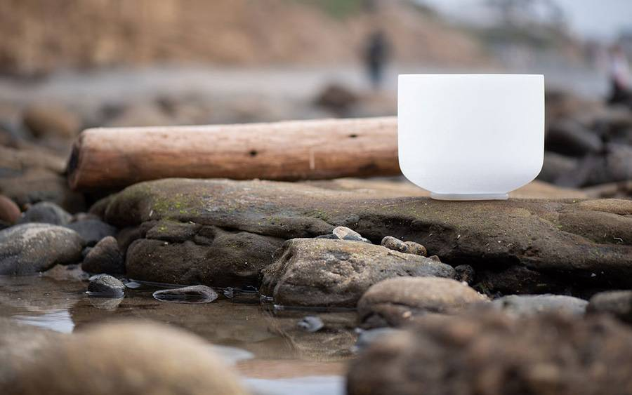 Photo of white singing bowl on rocks in a small stream, representing the healing atmosphere of restorative yoga.