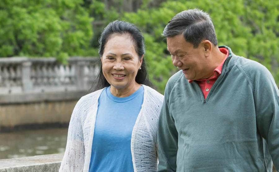 A smiling mature Asian couple represents the power and value of knowing skin cancer symptoms.